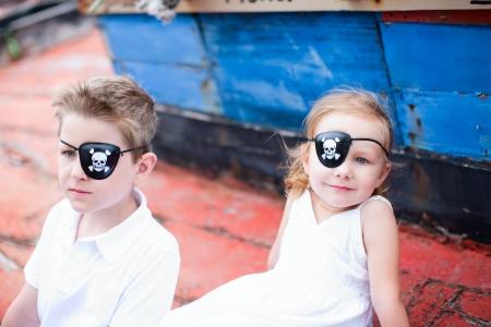 Chico lindo piratas y una niña sentada en el barco viejo Foto de archivo - 15690713