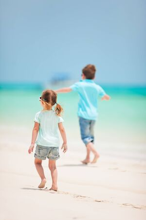 Back view of small kids running at tropical beach photo