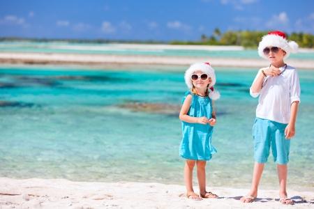 Boy and girl wearing Santa hats at tropical beach photo