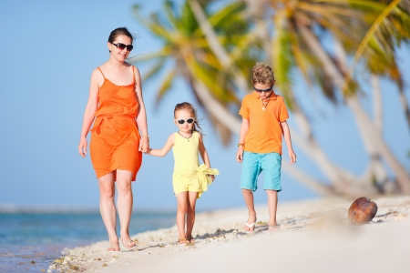 Beautiful mother and two kids enjoying beach vacation photo