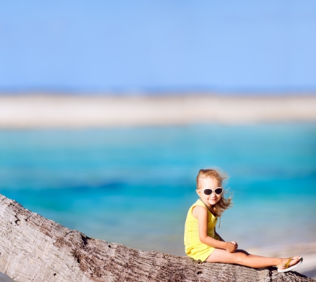 Little girl sitting on a coconut palm photo