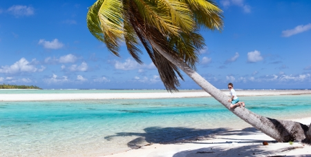 polynesia: Little boy sitting on palm at exotic beach