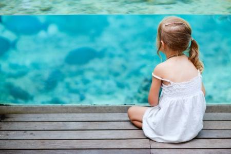 personnes de dos: Petite fille profiter de la vie sous-marine de la mer � travers la paroi vitr�e