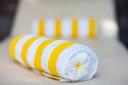towels luxury: White and yellow towels decorated with frangipani flowers in a tropical resort Stock Photo