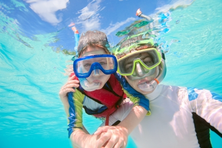 underwater sport: Underwater portrait of father and son snorkeling together Stock Photo