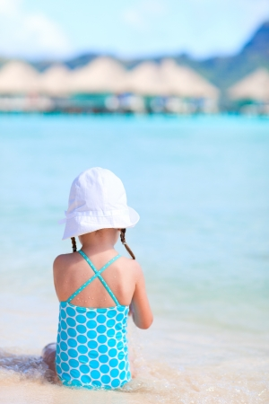little girl swimsuit: Back view of a little girl at shallow water on a tropical beach Stock Photo