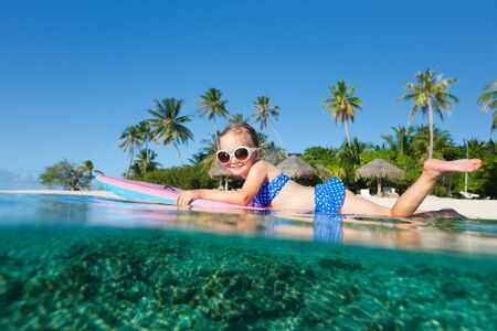 Adorable little girl on tropical vacation swimming in ocean photo