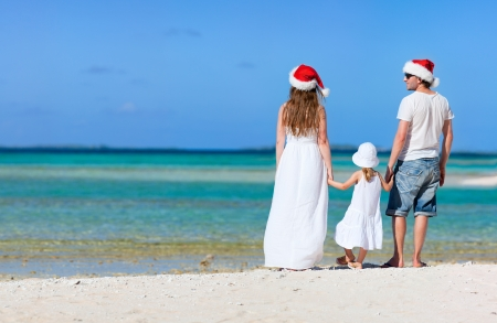 beach hat: Young parents in Santa hats and their little daughter on a tropical beach Stock Photo