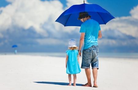 Vader en dochter op het strand met paraplu te verbergen tegen de zon Stockfoto