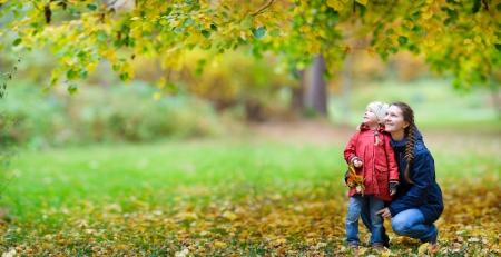 母と美しい秋の公園で彼女の小さな娘