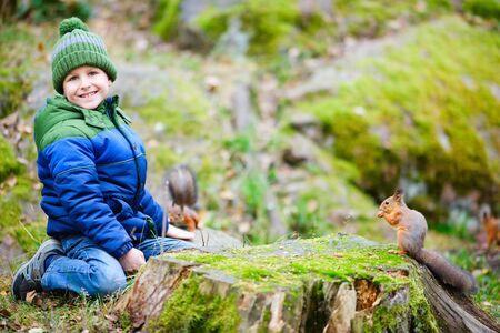 Cute boy feeding little squirrel at autumn park Stock Photo - 15892555