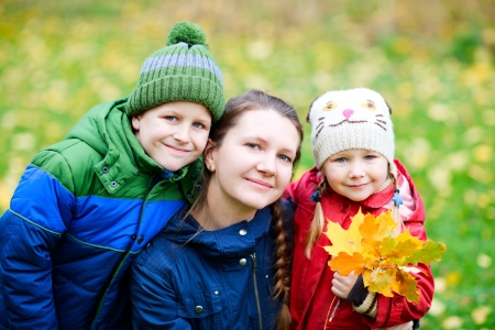 Portrait of mother and kids outdoors at beautiful autumn park photo