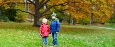 Brother and sister outdoors in a beautiful autumn park photo