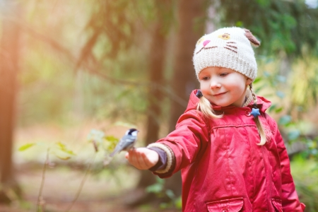 tit: Adorable little girl and great tit bird sitting on her finger Stock Photo