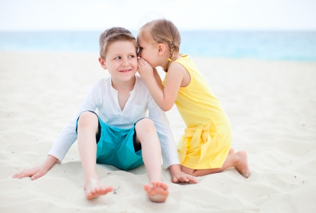 Adorable little girl telling a secret to her brother photo