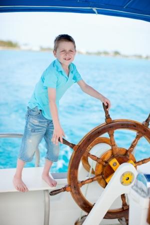 skipper: Cute little boy at sail boat wheel Stock Photo
