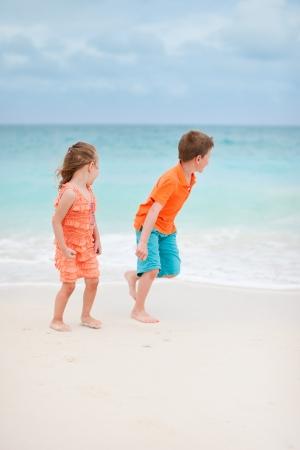 klein meisje op strand: Twee kinderen spelen op tropisch strand Stockfoto