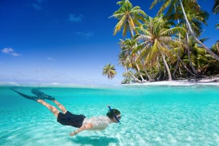 남자는 이국적인 섬 앞에 명확한 열대 바다에서 수영