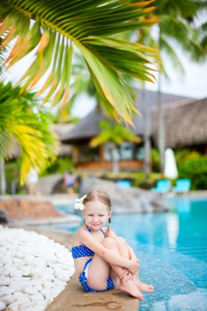 Portrait of adorable little girl sitting near a swimming pool photo