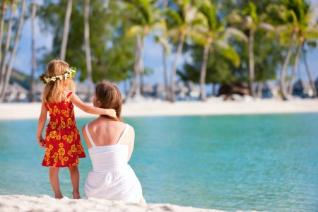 bora: Back view of mother and daughter wearing Polynesian dress on a tropical beach
