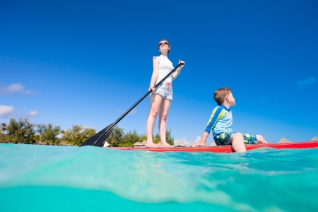Mother and son paddling on stand up paddle board at tropical ocean