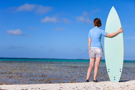 Back view of young woman with surfboard photo
