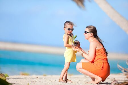 Mother and daughter holding small coconut sprout at tropical beach photo