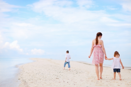 Mother and two kids walking at tropical beach photo