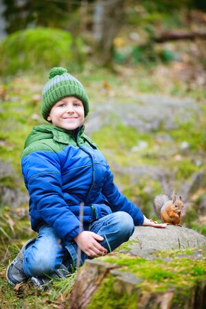 Cute boy feeding little squirrel at autumn park photo