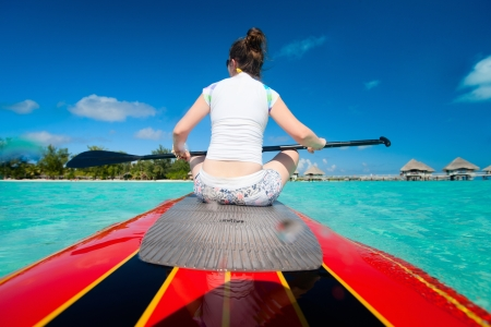 polynesia: Back view of young sporty woman on paddle board