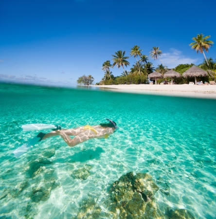 bora bora: Woman swimming in a tropical lagoon in front of exotic island Stock Photo