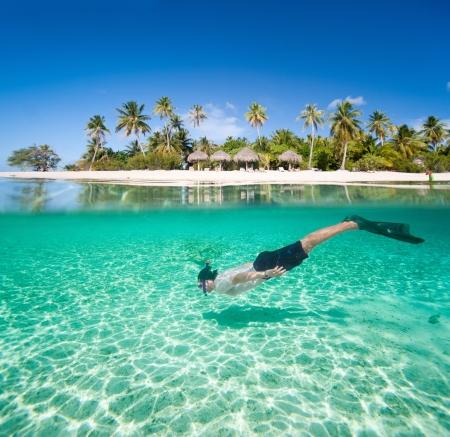 이국적인 섬 앞의 열 대 라군에서 수영하는 사람 (남자)