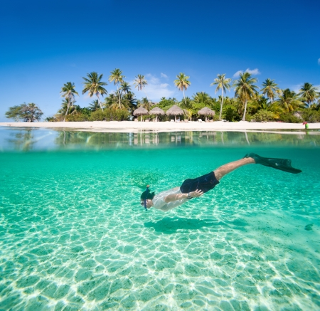 bora: Man swimming in a tropical lagoon in front of exotic island