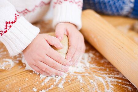 Close up of little girl kneading dough photo