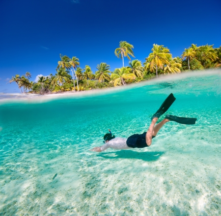 diving equipment: Man swimming underwater in a tropical lagoon