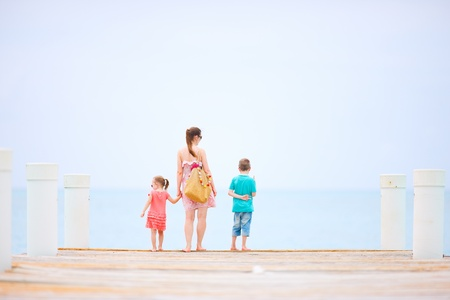 Back view of mother and kids outdoors on a wooden dock photo