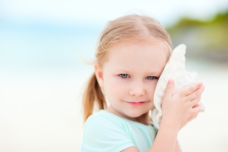 conch: Portrait of adorable little girl with a seashell
