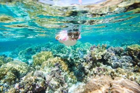 Underwater portrait of woman snorkeling at coral reef Stock Photo