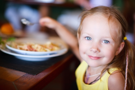 child food: Portrait of adorable little girl having lunch Stock Photo