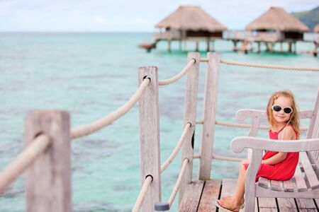 Little girl at terrace of over water bungalow photo