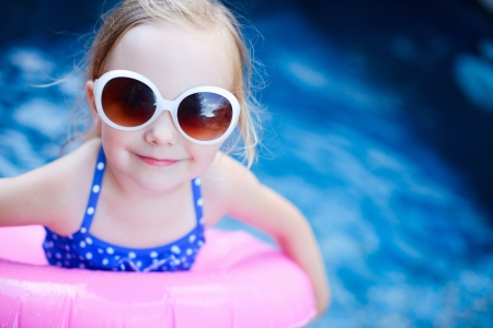 Adorable little girl with inflatable ring at swimming pool