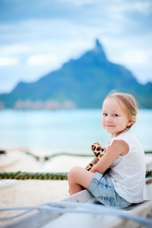 Little girl on vacation on Bora Bora island with Otemanu mountain silhouette on background photo