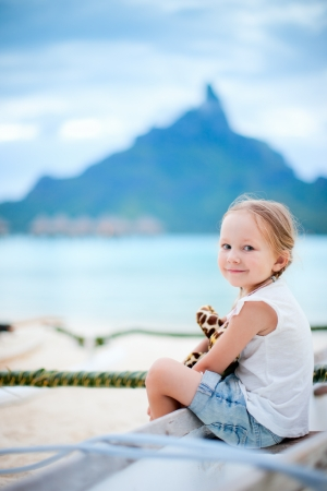 otemanu: Little girl on vacation on Bora Bora island with Otemanu mountain silhouette on background