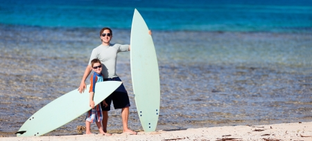 Father and son with surfboards at beach enjoying vacation photo