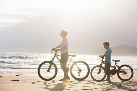 familia viaje: Madre e hijo con bicicletas en la playa al atardecer Foto de archivo