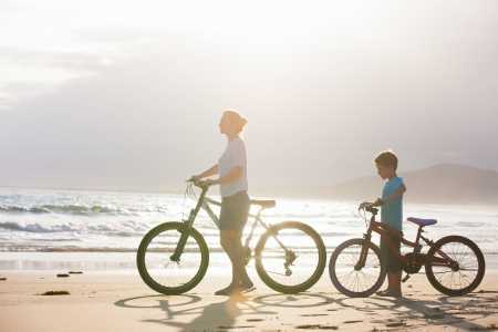 woman bike: Mother and son with bikes on a beach at sunset