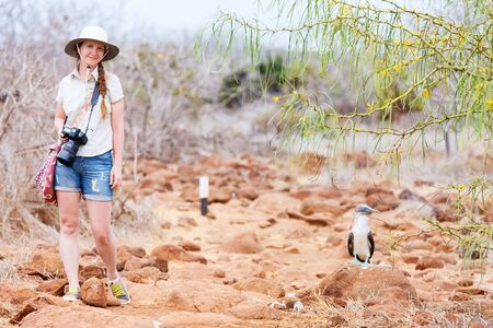 Female tourist near blue footed booby at Galapagos island of  North Seymour Stock Photo - 17500469