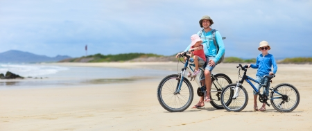 Father and kids riding bikes along a beach photo