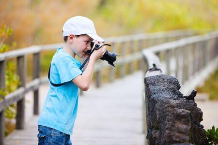 ecotourism: Little boy photographing black marine iguanas
