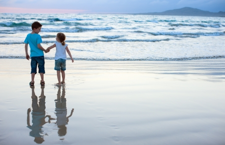 Brother and sister on beach at sunset Stock Photo - 17603585